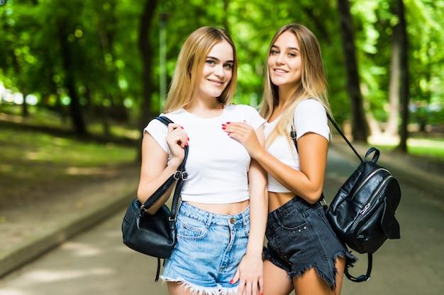 Duas lindas meninas andando no parque de verão.
