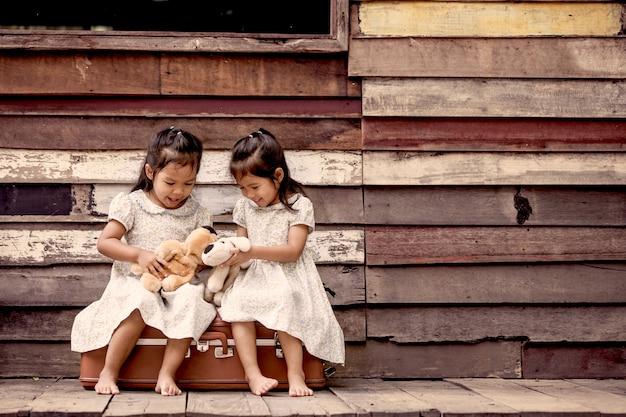Duas lindas meninas asiáticas brincando com os ursos de pelúcia.