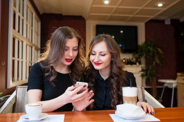 Duas lindas meninas bebem café e olham no telefone