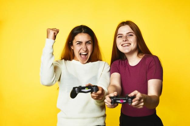 Duas lindas meninas caucasianas com joystick sem fio