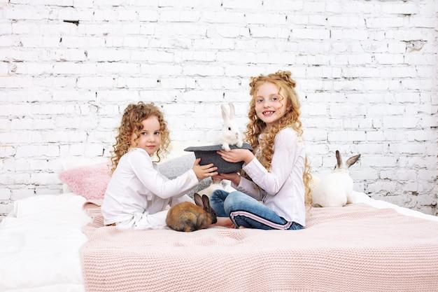 Duas lindas meninas crianças com cabelo encaracolado e coelhos fofinhos estão sentadas na cama em casa