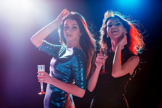 Duas lindas meninas dançando na festa bebendo champanhe