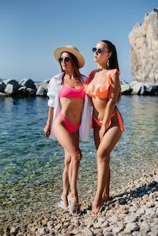 Duas lindas meninas de óculos e biquínis estão de pé e se divertindo na costa do oceano, no contexto de pedras enormes em um dia ensolarado. turismo e viagens turísticas.