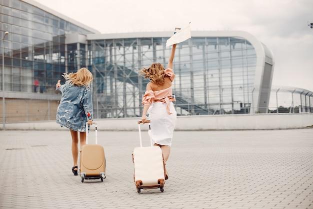 Duas lindas meninas em pé no aeroporto