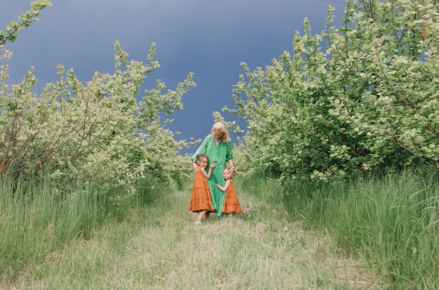 Duas lindas meninas em vestidos idênticos abraçando a mãe no pomar de maçãs antes da chuva. mãe carinhosa infância feliz