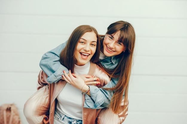 Duas lindas meninas estão andando pela cidade