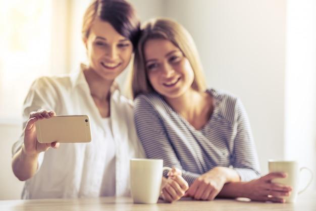 Duas lindas meninas estão fazendo selfie usando um smartphone.