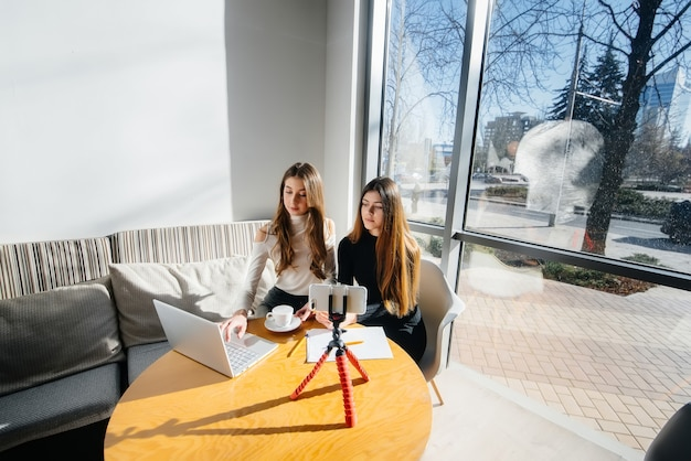 Duas lindas meninas estão sentadas em um café, gravando blogs de vídeo e se comunicando nas redes sociais.