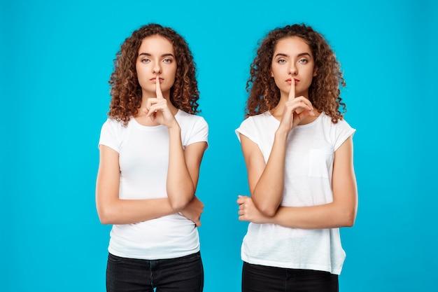 Duas lindas meninas gêmeas mostrando manter silêncio sobre parede azul