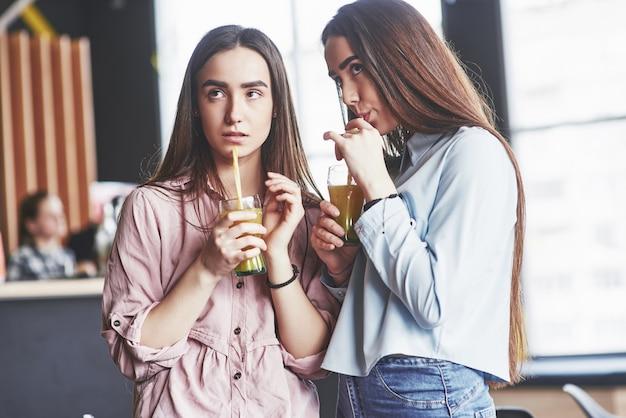 Duas lindas meninas gêmeas passam tempo bebendo suco. irmãs relaxando em um café e se divertindo juntos e sussurrando