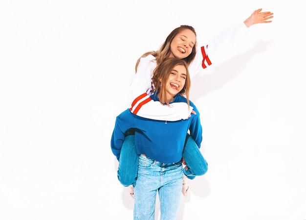Duas lindas meninas sorridentes em roupas da moda no verão. mulheres despreocupadas. modelo positivo, sentado nas costas da amiga e levantando as mãos