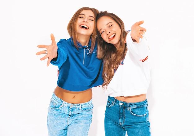Duas lindas meninas sorridentes em roupas da moda no verão. mulheres despreocupadas. modelos positivos