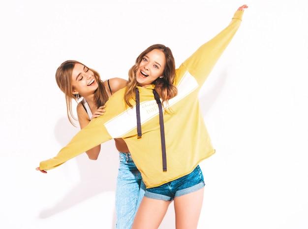 Duas lindas meninas sorridentes em roupas da moda verão jeans. mulheres despreocupadas. modelos positivos e mãos levantadas
