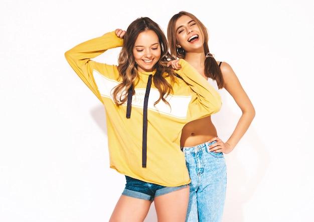 Duas lindas meninas sorridentes em roupas da moda verão jeans. mulheres despreocupadas. modelos positivos