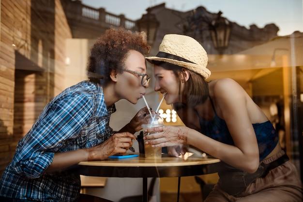 Duas lindas meninas sorrindo, bebendo de tubos, descansando no café. fora tiro.