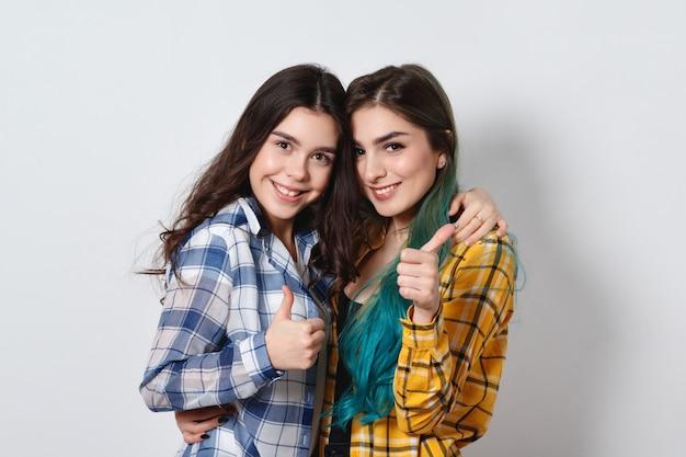 Duas lindas meninas, sorrindo e mostrando os polegares em branco