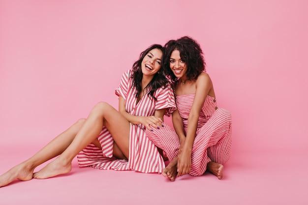 Duas lindas mulheres afro-americanas com aparência de modelo com lindas pernas longas, sorrindo alegremente e posando