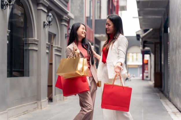 Duas lindas mulheres asiáticas com sacolas de compras na cidade sobre o fundo do shopping