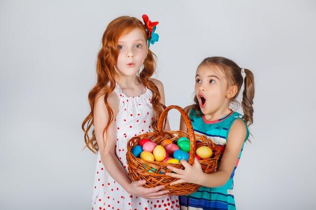 Duas lindas mulheres brilhantes, segurando uma cesta de ovos de páscoa. momentos engraçados.