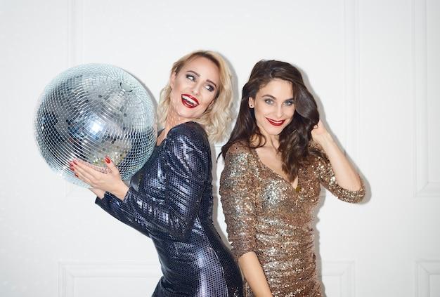 Duas lindas mulheres com bola de discoteca