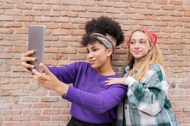 Duas lindas mulheres de diferentes raças, tirando selfie