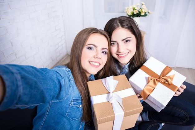 Duas lindas mulheres felizes tirando foto de selfie com presentes na sala de estar