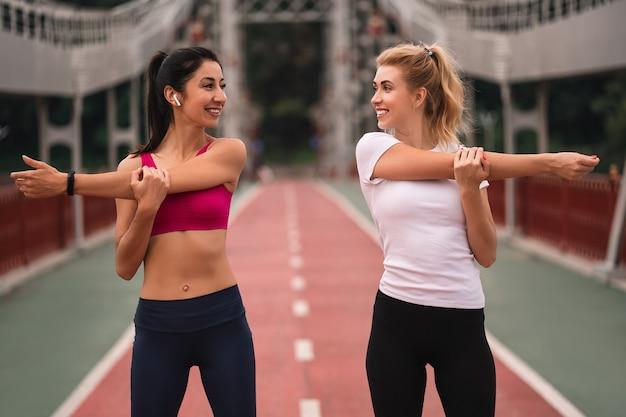 Duas lindas mulheres fitness sorrindo fazendo exercícios de alongamento esticando os braços enquanto se olham e ficam de pé na ponte