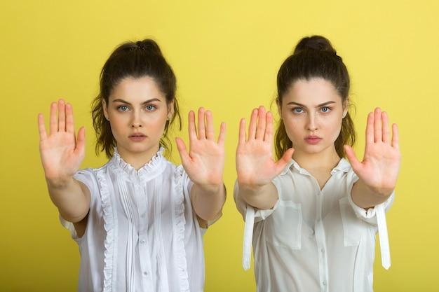 Duas lindas mulheres gêmeas alegres em fundo amarelo com gesto de mão