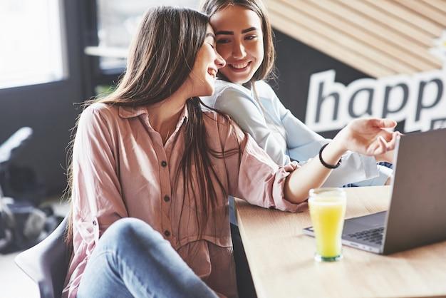 Duas lindas mulheres gêmeas passam tempo bebendo suco. irmãs relaxando em um café e se divertindo juntos