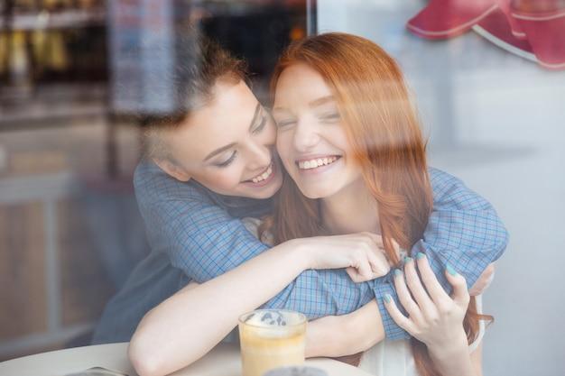 Duas lindas mulheres jovens felizes se abraçando no café