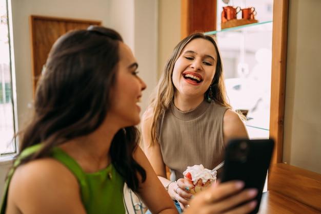 Duas lindas mulheres latinas animadas assistem a um vídeo engraçado em um celular moderno
