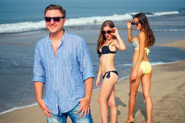 Duas lindas mulheres olham com olhos apaixonados para um homem solteiro caminhando na praia