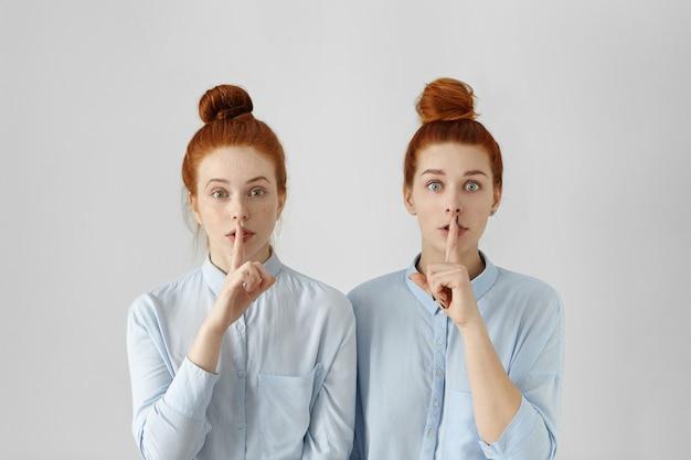 Duas lindas mulheres ruivas com os mesmos coques de cabelo, vestidas com camisas formais idênticas