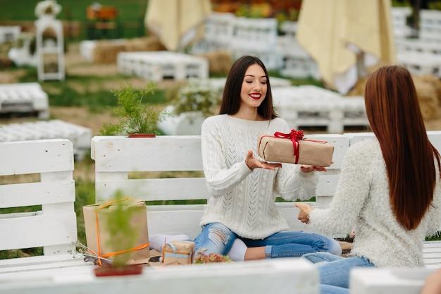 Duas lindas mulheres sentadas em um banco jogando presentes uma para a outra