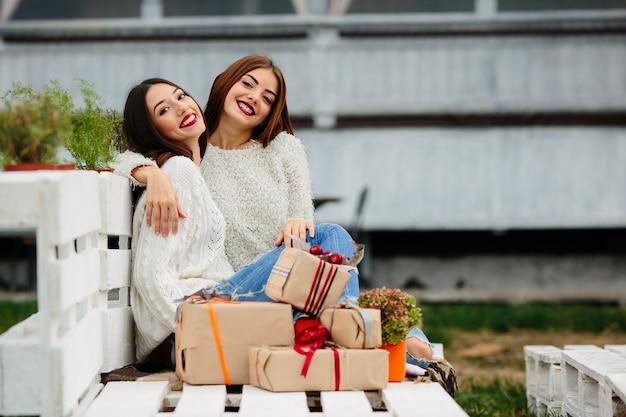 Duas lindas mulheres sentadas em um banco, segurando presentes nas mãos e olhando