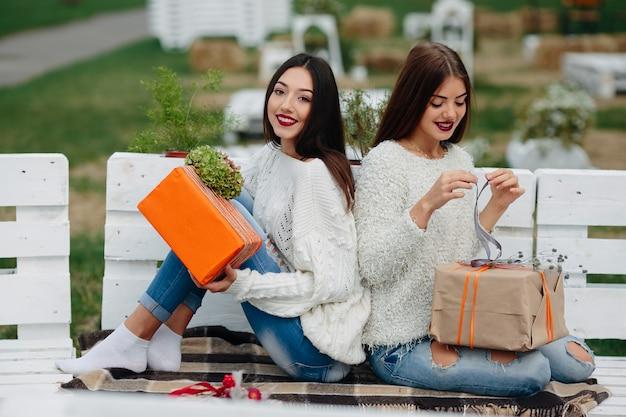 Duas lindas mulheres sentadas em um banco segurando presentes nas mãos