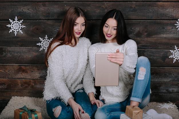 Duas lindas mulheres sentadas no chão com um tablet, entre os presentes de natal
