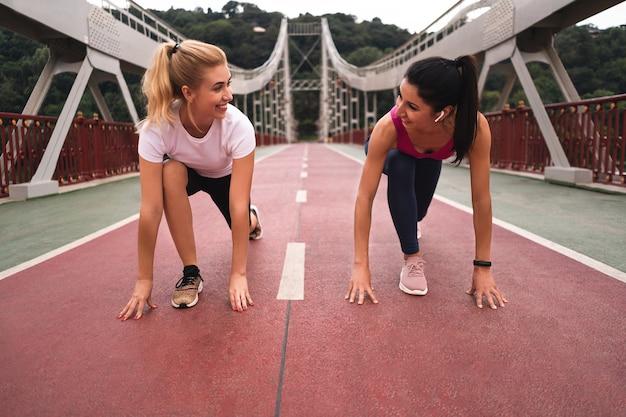 Duas lindas mulheres sorridentes em roupas esportivas se aquecendo antes de correr na ponte ao ar livre, olhando uma para a outra