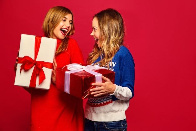Duas lindas mulheres sorridentes em suéteres elegantes e grandes caixas de presente