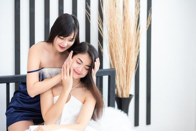 Duas lindas mulheres tailandesas. ela estava de pijama e sentada na cama. conceitos homossexuais e lésbicos Foto Premium