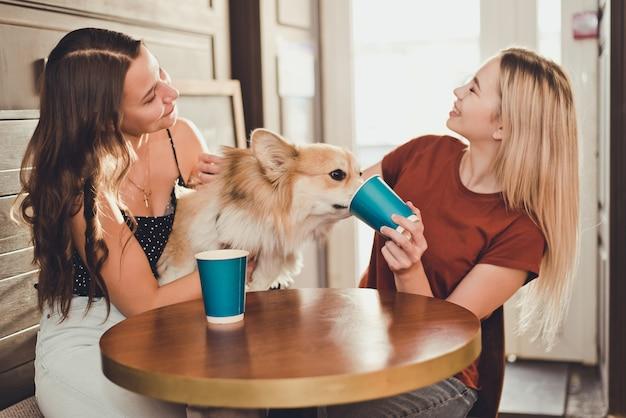 Duas lindas mulheres tomando café com um cachorro corgi