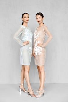 Duas lindas mulheres usando vestidos transparentes claros com detalhes em renda posando de maneira idêntica