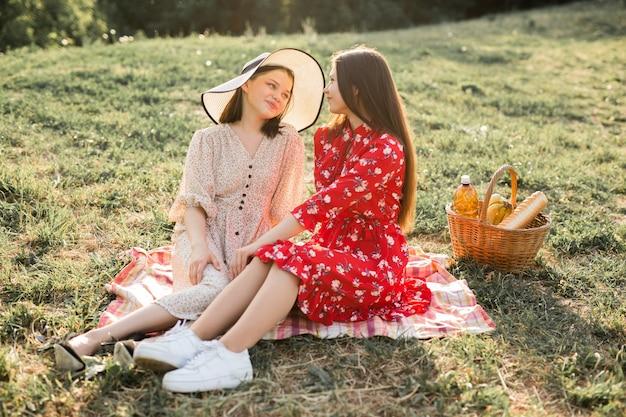 Duas lindas namoradas jovens no parque de verão na grama
