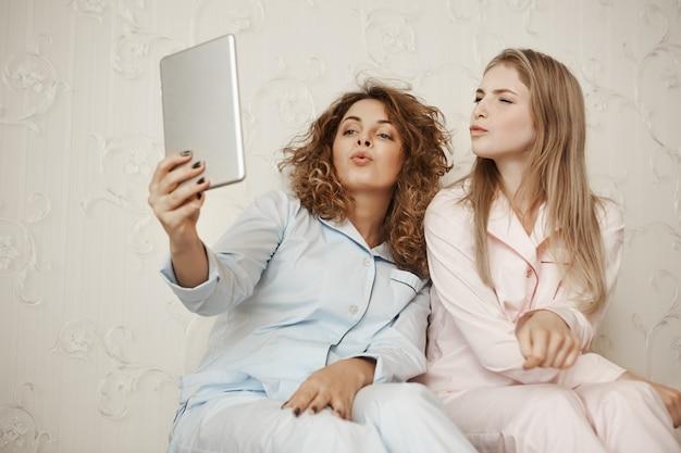 Duas lindas namoradas sentadas em casa em roupas de dormir se divertindo enquanto toma selfie com tablet digital, dobrando os lábios como se estivesse mandando um beijo no ar, expressando simpatia e felicidade