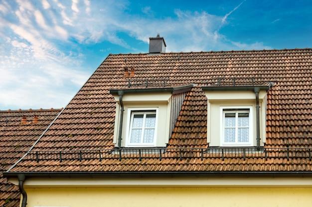 Duas lucarnas com marés em uma casa com telhado de telhas.