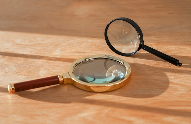 Duas lupas na mesa de madeira com o conceito de luz do dia de observação, exploração, estudo e pesquisa