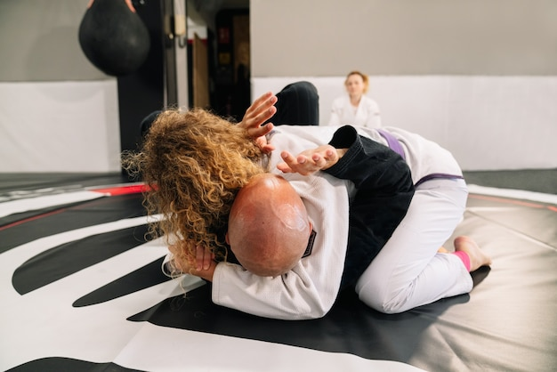 Duas lutadoras de judô de artes marciais praticando novas técnicas em um tapete de ginástica