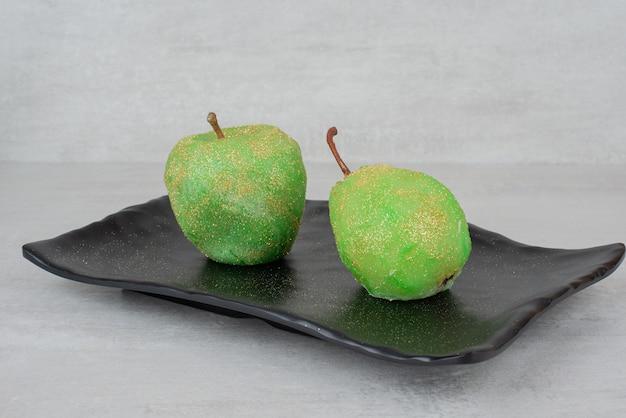 Duas maçãs brilhantes na placa preta na superfície branca.