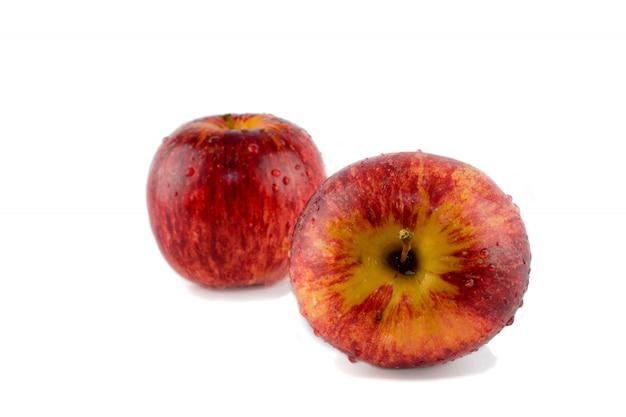 Duas maçãs listradas vermelhas da água da gota. isolado contra o fundo branco