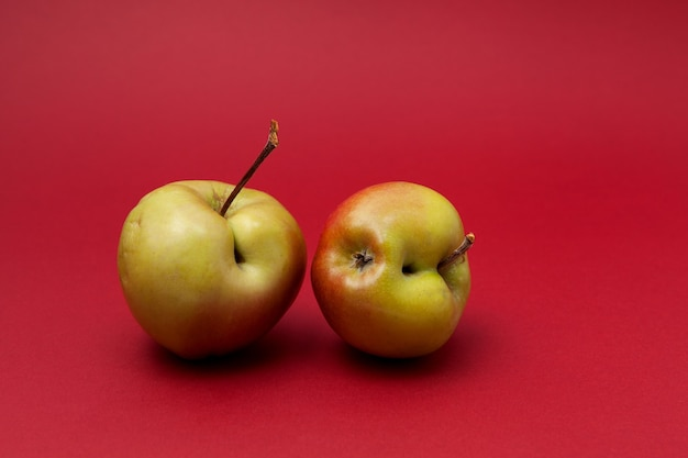 Duas maçãs verdes feias com falhas em fundo vermelho. conceito - redução do desperdício de alimentos. uso na culinária de produtos imperfeitos.